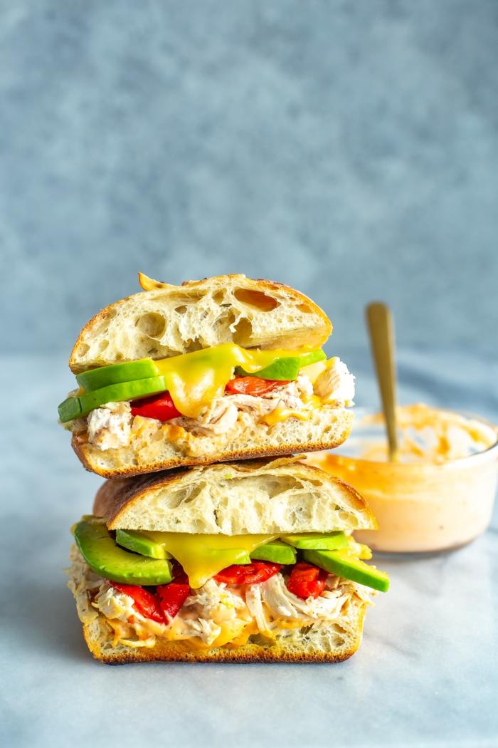 kleiner löffel und senf zwei sandwiches mit avocado und frischen tomaten