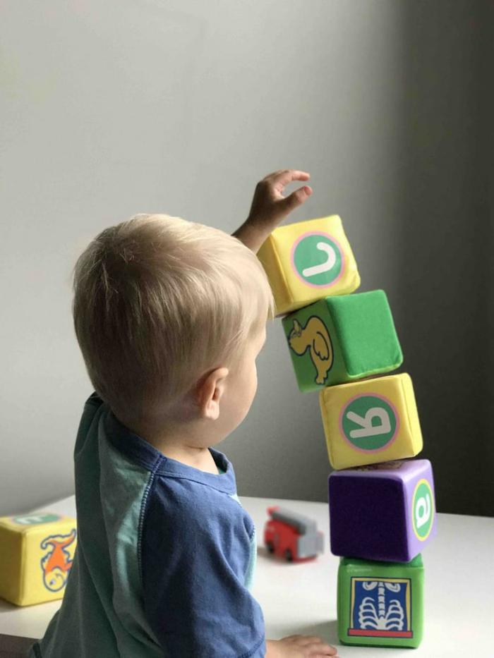 kleines kind spielt mit blöcken lernturm für kinder wichtige informationen