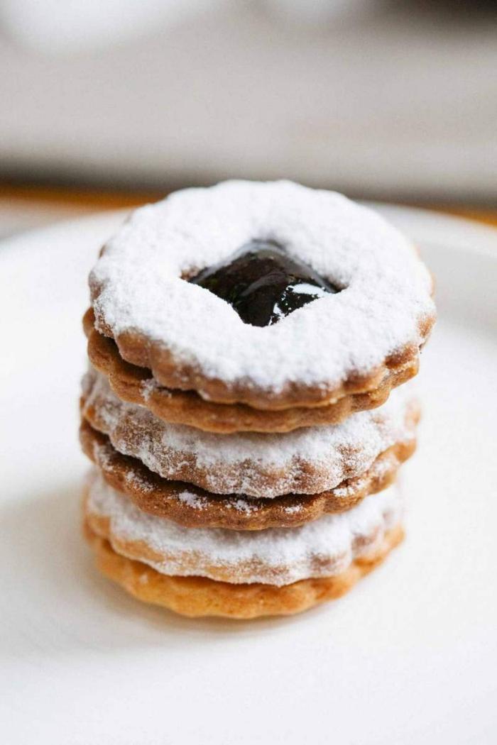 leckere ideen für weihnachtsplätzchen mit marmelade spitzbuben plätzchen bestreut mit puderzucker drei aufeinander gestellte kekse