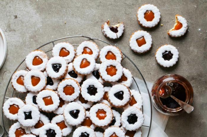 linzer kekse mit marmelade verschiedene sorte spitzbuben mit mandeln bestreut mit puderzucker einmachglas mit aprikosenmarmelade