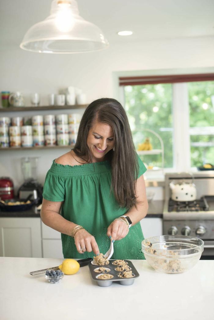 low carb muffins blaubeeren mandelmehl frau mit grüner bluse in der küche