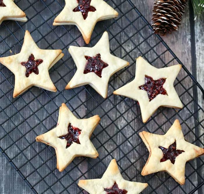 marmelade kekse spitzbuben plätzchen in sternform auf einem grillrost dekoration mit zapfen weihnachtsgebäck selber machen