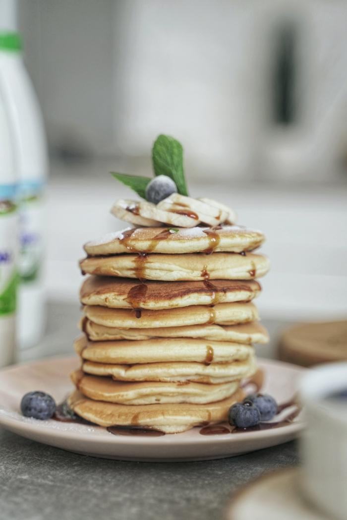 minze und kleine blaubeeren ein teller mit kleinen veganen pfannkuchen