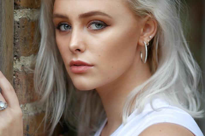 natürliches make up eine junge frau mit grauen haaren und weißen ohrringen