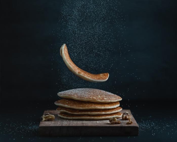 puderzucker und ein teller mit veganen pfannkuchen mit blaubeeren