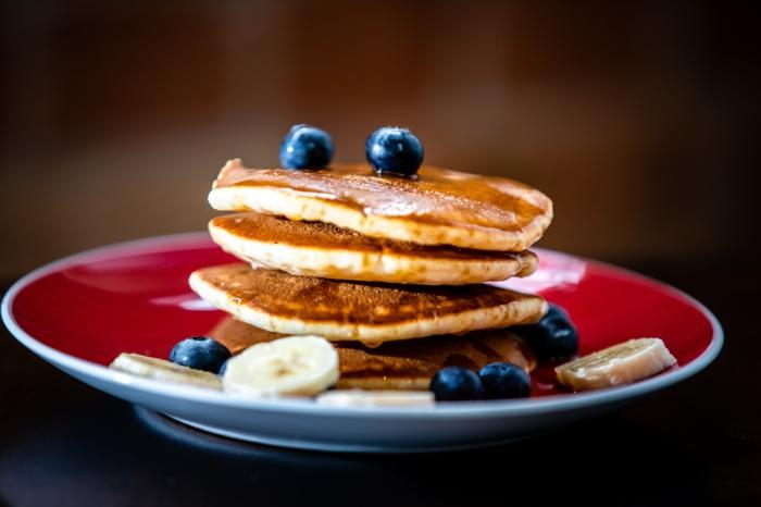 roter teller mit kleinen pfannkuchen mit blaubeeren und banane pfannkuchen füllen