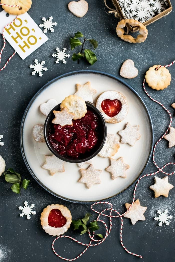 schwarze schale mit erdbeermarmelade kreative weihnachtsdekoration kekse in sternform spitzbuben mit mandeln schneeflocken aus papier
