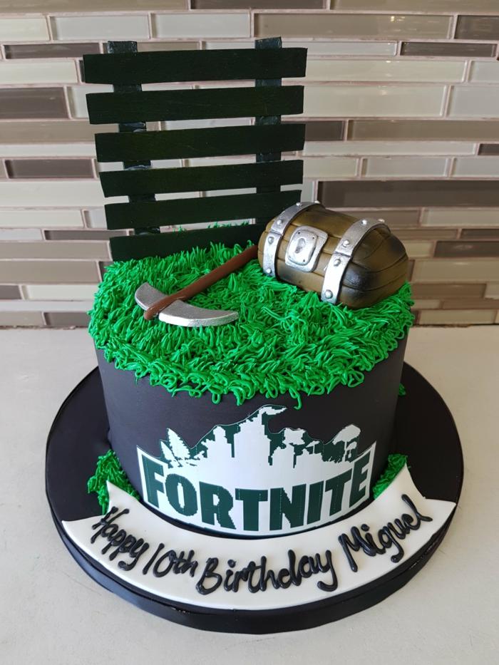 schwarze torte mit grüner dekorationö figur von truhe und axt teenager geburtstag kuchen inspiration fortnite tortendeko ideen