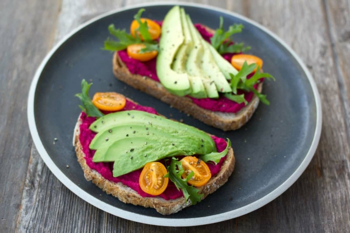 schwazer teller mit zwei stullen mit tomaten und salat ideen für veganes gesundes abenbrot mit avocado