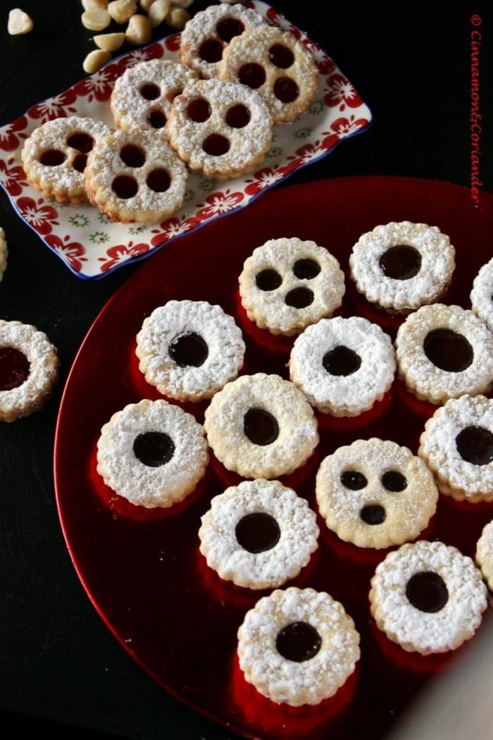 spitzbuben mit mandeln macadamia und kirschenmarmelade roter teller mit weihnachtsplätzchen bestreut mit puderzucker