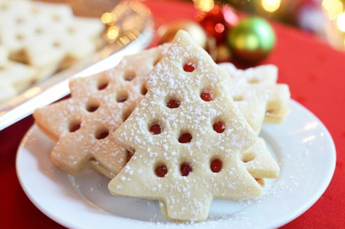 tannenbaum weihnachtsplätzchen mit marmelade spitzbuben kekse weihnachtsgebäck ideen plätzchen auf einem weißen teller tisch mit roter tischdecke bunte weihnachtskugeln