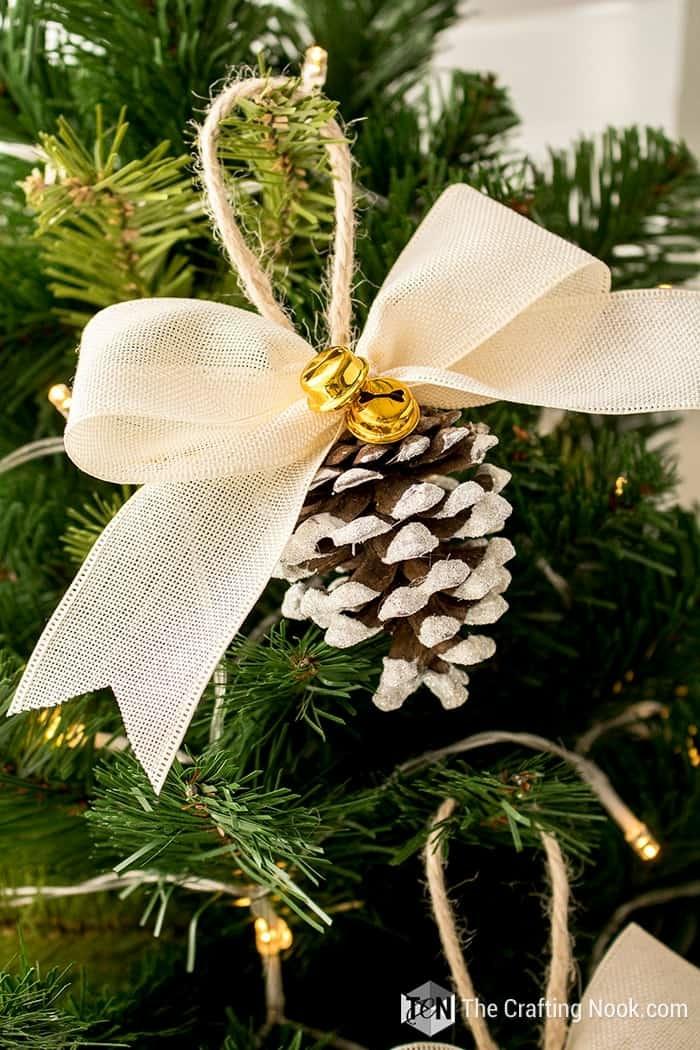 tannezapfen mit weißer schleife und kleiner glocke dekoration weihnachtsbaum ideen und inspiration