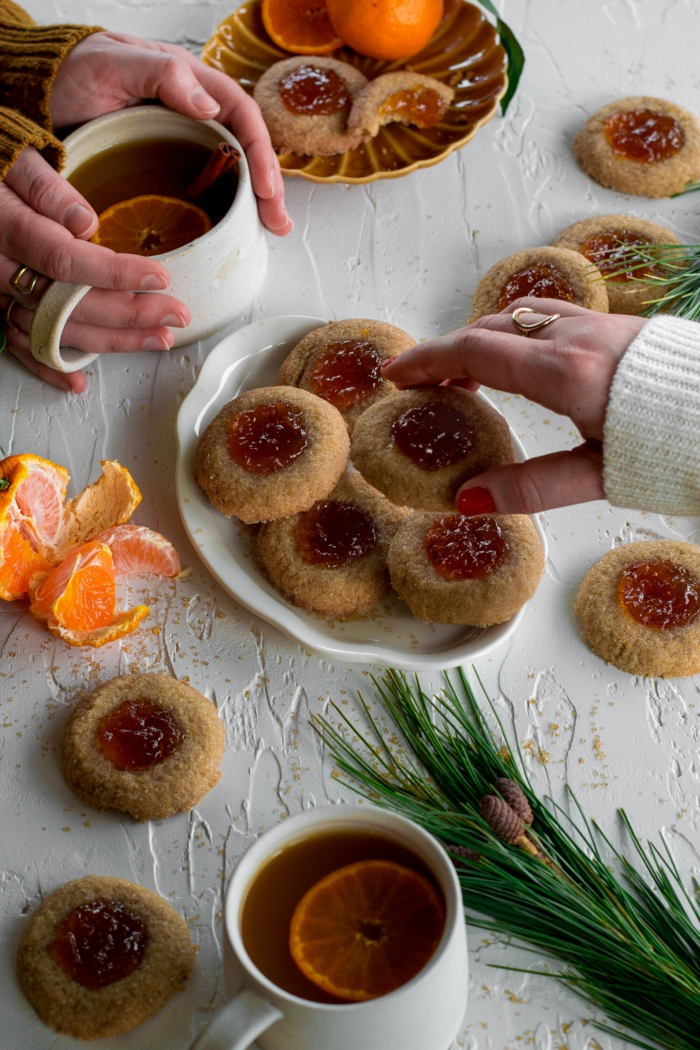 tassen mit tee zitronenscheiben gedeckter tisch mit weißer tischdecke engelsaugen plätzchen rezepte mit marmelade dekoration tannenzweig