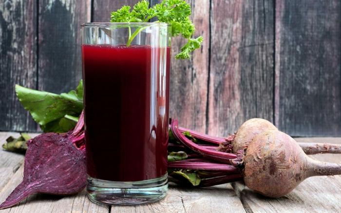 tisch aus holz hausmittel die das immunsystem stärken ein glas mit saft aus roter beete