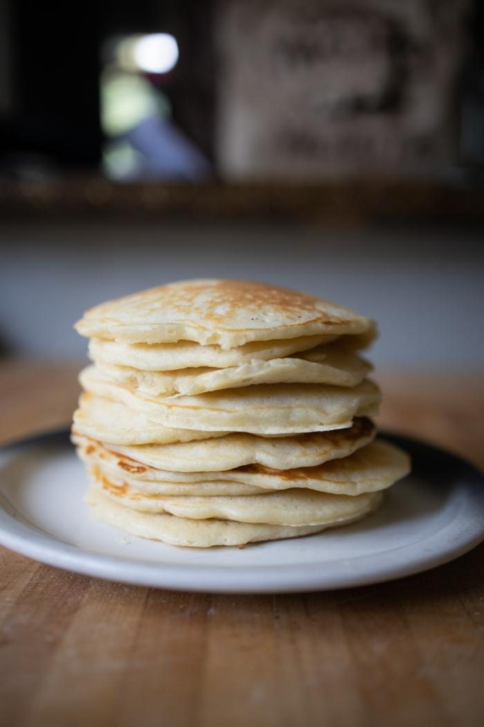 tisch aus holz und ein weißer teller mit vielen kleinen pfannkuchen mit puderzucker