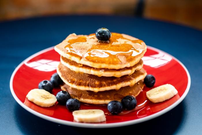 vegane pfannkuchen füllen ein kleiner rpter teller mit kleinen blaubeeren und bananen