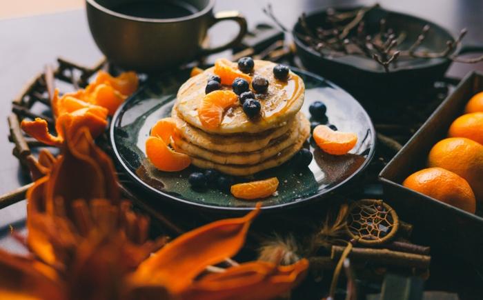 vegane pfannkuchen füllen mit blaubeeren und orangen mandarinen graue tasse