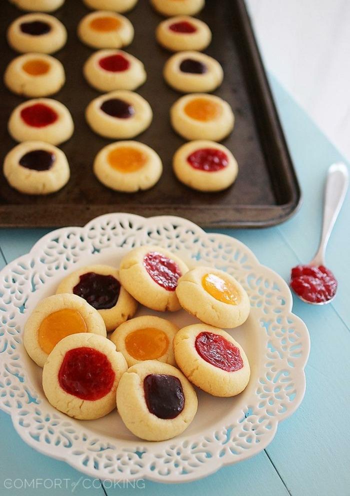 weißer teller mit engelsaugen kekse mit verschiedenen sorten marmelade beste weihnachtsplätzchen schwarzer backblech mit weihnachtsgebäck