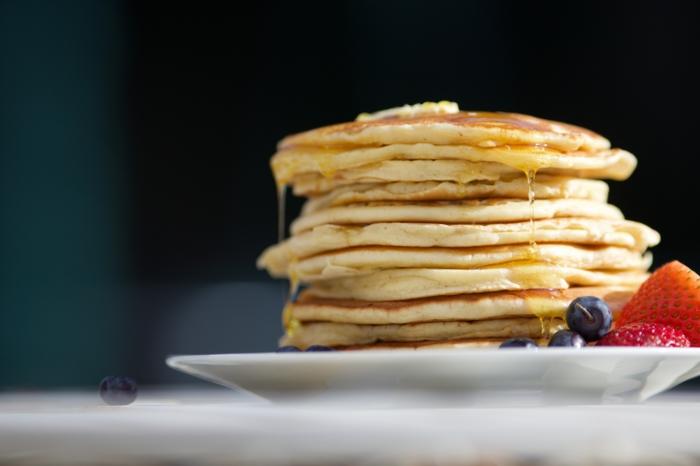 weißer teller mit veganen pfannkuchen mit blaubeeren puderzucker und blaubeeren