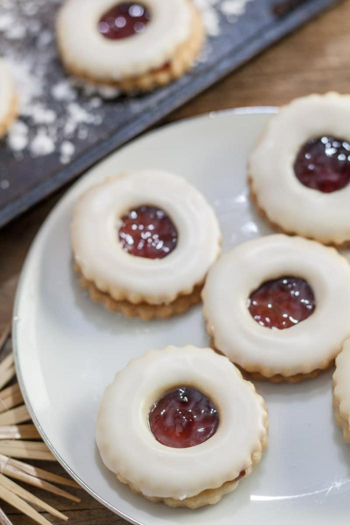 weißer teller mit weihnachtskeksen mit marmelade und vanillecreme leckere spitzbuben plätzchen für weihnachten backen leckere rezepte