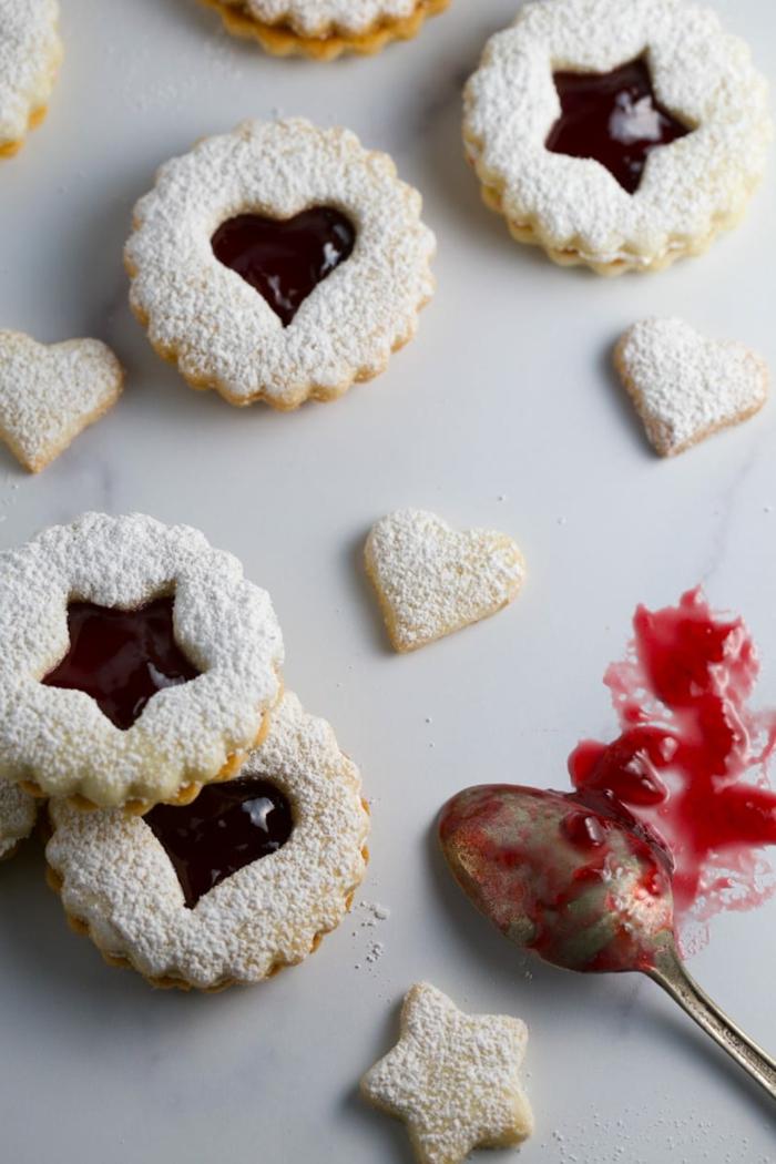 weihnachten kekse backen spitzbuben mit mandeln himbeermarmelade mit sternen und herz formen löffel mit marmelade