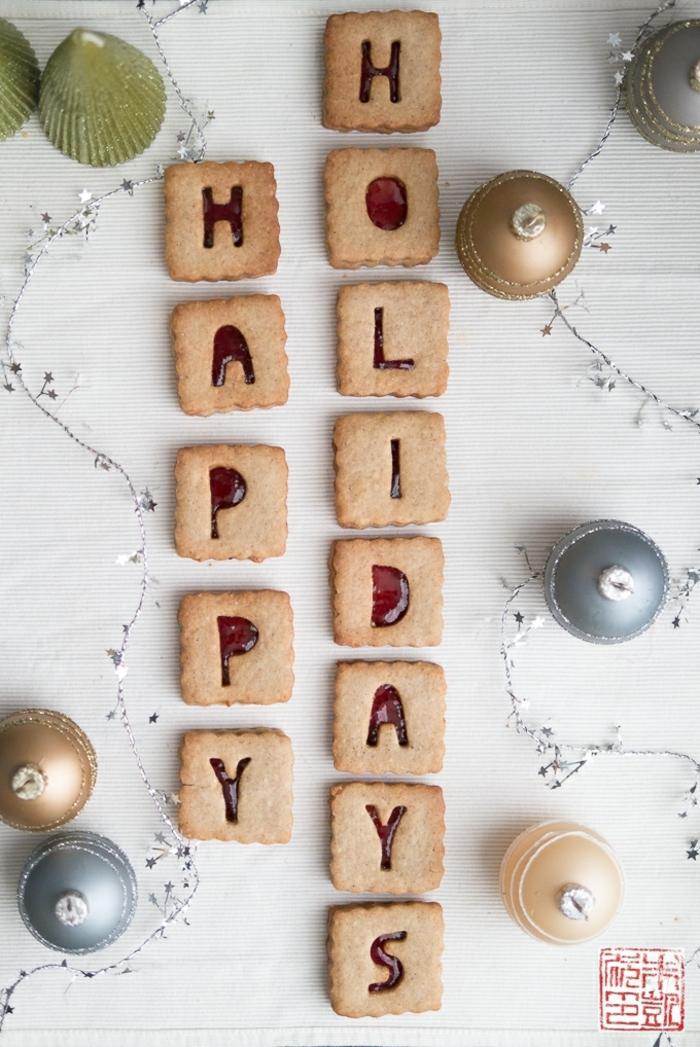 weihnachten kekse plätzchen mit marmelade aus cranberrys happy holidays aufschrift goldene und silberne weihnachtskugeln schöne weihnachtsdekorartion große grün bemalte muschel