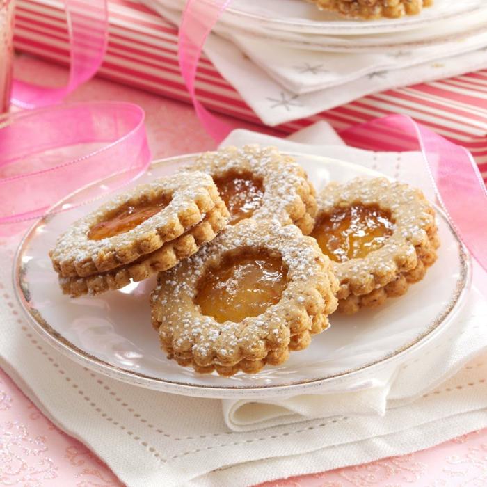 weihnachtsdessets inspiration linzer kekse mit aprikosenmarmelade auf einem teller engelsaugen plätzchen marmelade