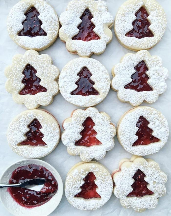 weihnachtsplätzchen mit marmelade mit tannenbaum form auf einem backblech kekse bestreut mit puderzucker