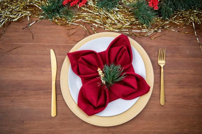 weihnachtsstern poinsettie falten schöne tischdeko weihnachten servietten falten anleitung goldener besteck rote serviette tannezweige deko
