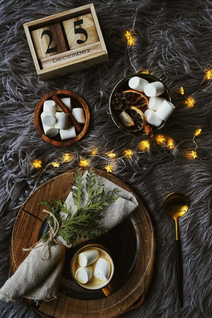 weihnachtstisch kreativ dekorieren teller aus holz servietten falten modern tannenzweig deko kleine lichterketten marschmallows flauschige graue decke