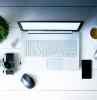 büro einrichten große kopfhörer grüne pflanze tasse mit kaffee fotoaparat schwarzes handy mac book laptop