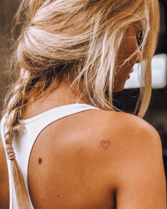 blonde frau lange haare im zopf weißes top originelle tattoo ideen minimalistisch kleines schwarzes herz tätowierung