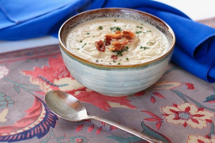 decke mit blumen eine weiße suppe mit speck und frischen grünen kräutern