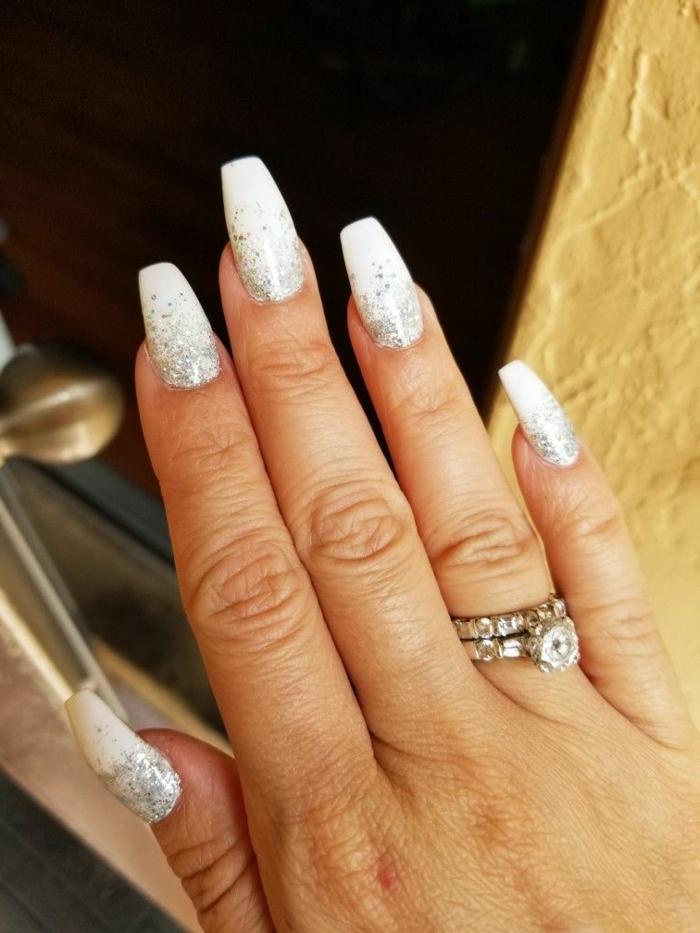eleganter finger am ringfinger lange fingernägel mit maniküre weiße nägel glitter ombre