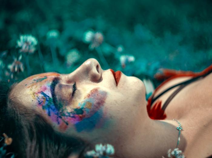essenza nobile de frauen kosmetik und schönheit frau im gras liegend gefärbtes gesicht träumt
