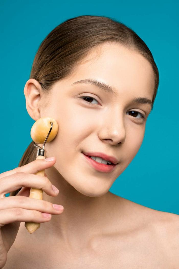 essenza nobile de kosmetik schönes gesicht gesund jade roller gesichtsmassage junge frau mit jade roller lächelt