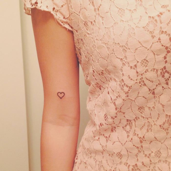 frau im blass pinkes kleid symbole für stärke kraft mut tattoo kleines herz schwarz ideen und inspo
