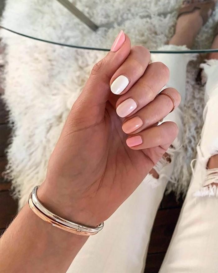 frau in weißen jeans goldene armbänder nägel in verschiedene farben lackiert kurze ovale nagelform gelnägel inspo