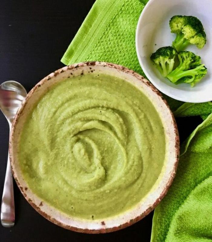 grüne suppe mit brokkoli und mit frischen petersilienblätern ein löffel eine grüne decke