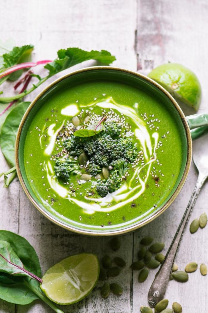 grüne zitronen und eine schüssel mit grüner suppe eine suppe mit sahne und brokkoli
