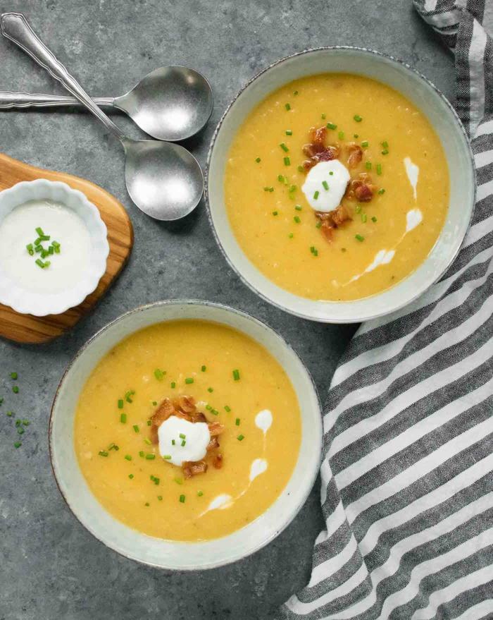 graue decke zwei schüsseln mit oranger suppe mit speck und meerrettich zwei löffel