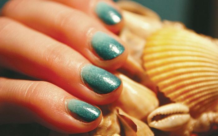 große muschel ombre nails in verschiedene blautöne dame mit moderner maniküre kurze fingernägel runde nagelform