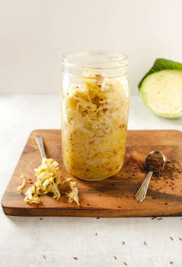 großen einmachglas mit sauerkraut zubereiten rezept gesunde ernährung und rezepte schneidebrett holz löffel mit gewürz