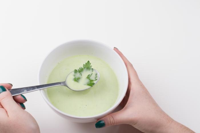 hände einer frau mit blauem nagellack eine suppe mit kartoffeln und petersile
