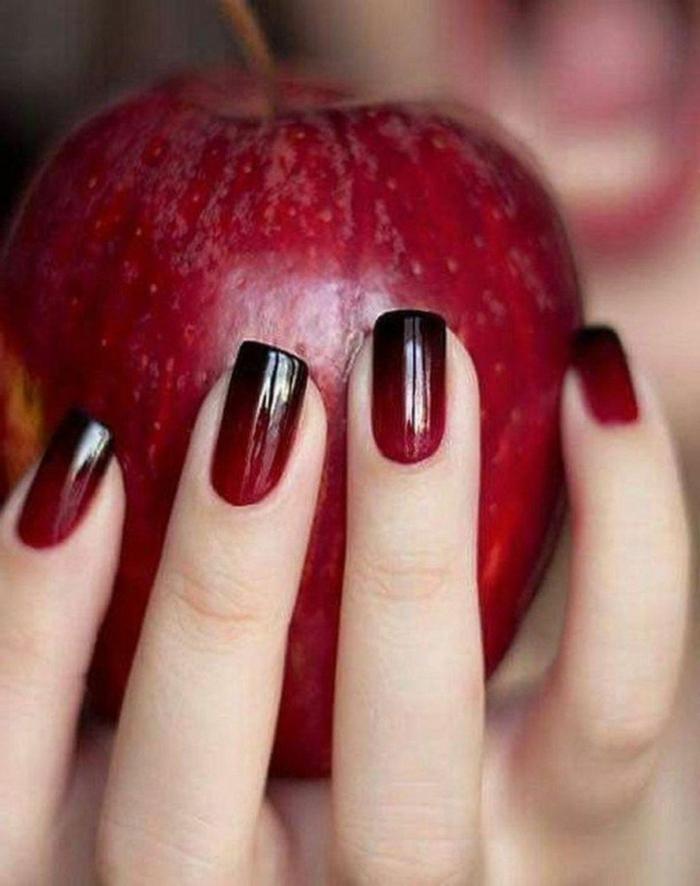 hand hält großen roten apfel schöne gelnägel ombre nägel schwarz rot verlaufend squoval nagelform kürzere nägel maniküre