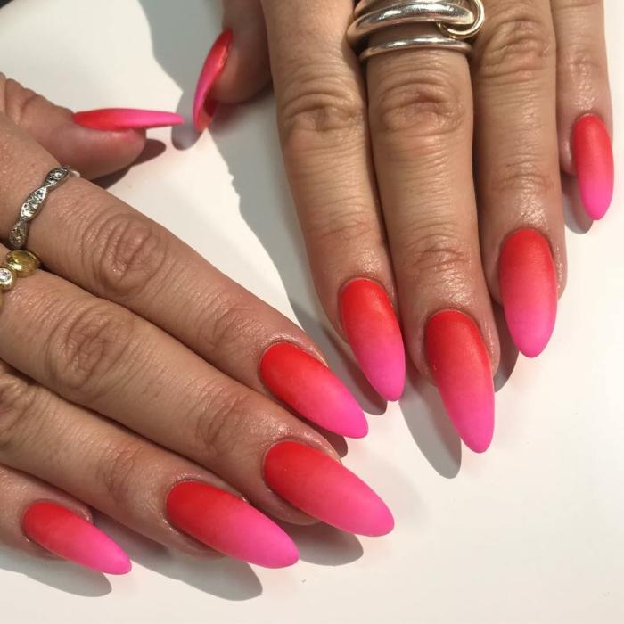 kreative inspiration maniküre lange fingernägel spitze form pinke und rote nagellackfarbe viele ringe an die finger schöne gelnägel