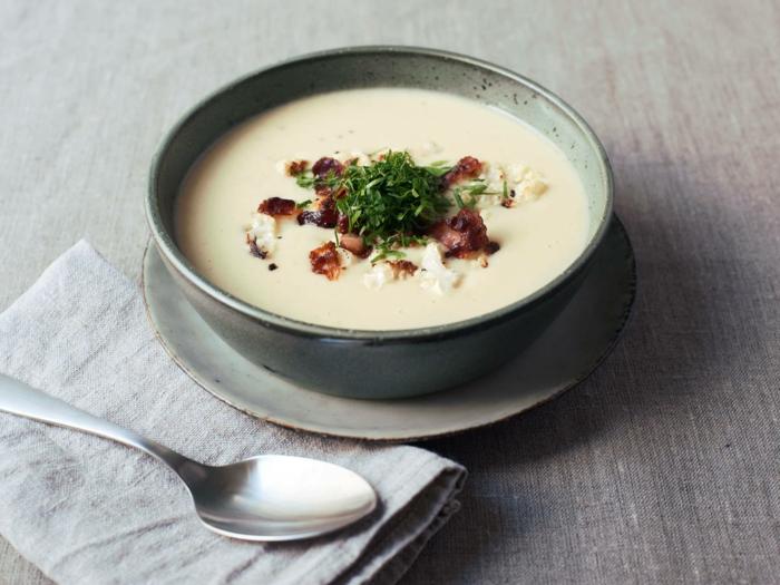 löffel und eine graue schüssel mit suppe mit frischen kräutern und speck eine graue decke
