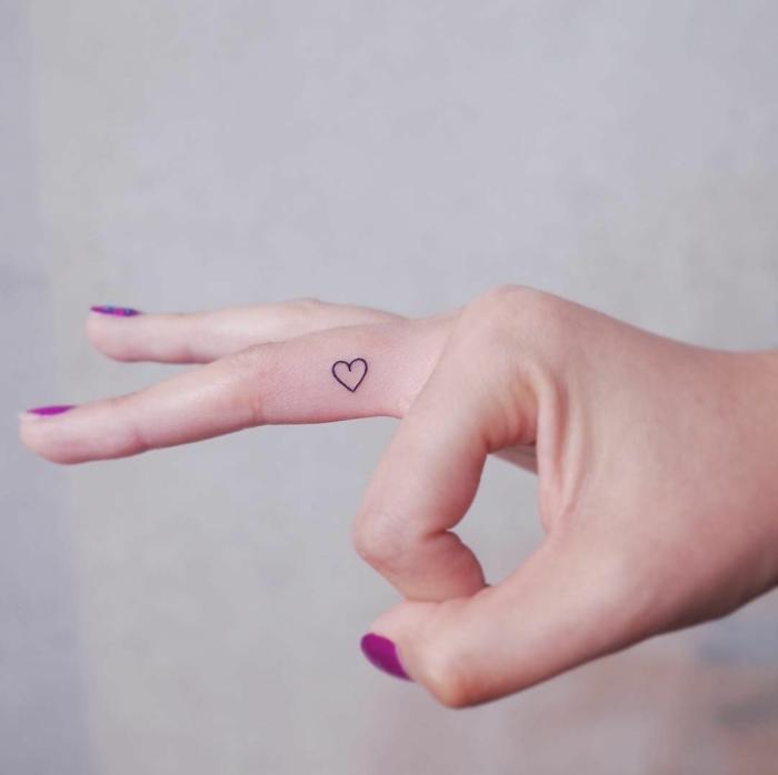 schöne maniküre lila lackierte fingernägel kleines herz tattoo am mittelfinger kleine tattoos frauen