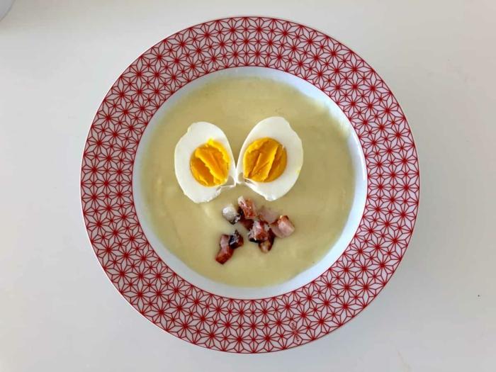 speck und zwei gekochte eier ein roter teller mit suppe mit meerrettich