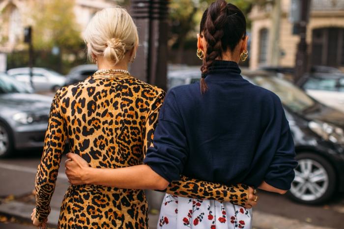 zwei elegante damen street style animal print kleid blonde und braune haare frisuren mittellanges haar inspo geflochtener pferdeschwanz